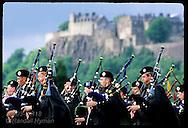 Pipe band performs below Stirling Castle, symbol of Scottish nationalism; July, Stirling. Scotland