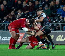 Ken Owens of Scarlets under pressure from Owen Watkin of Ospreys<br /> <br /> Photographer Simon King/Replay Images<br /> <br /> Guinness PRO14 Round 11 - Ospreys v Scarlets - Saturday 22nd December 2018 - Liberty Stadium - Swansea<br /> <br /> World Copyright © Replay Images . All rights reserved. info@replayimages.co.uk - http://replayimages.co.uk