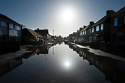 © London News Pictures. 16/02/2014. Egham, UK.  Properties reflected on flood water on a residential street in Egham, Surrey that has been hit heavily by flooding. Photo credit : Ben Cawthra/LNP