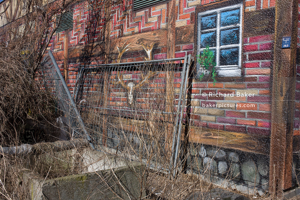 Sprayed or painted mural showing a country cabin landscape, on the side of an industrial building in Mauerpark - an open space on the site of the old Berlin wall, the former border between Communist East and West Berlin during the Cold War.