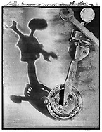 Solaroid - At The Circus - The Unicycle - This series was inspired by Circus Archaos in 1989 to create a circus made up of characters constructed from rusty objects and depicted by shadows. The print surface is overlaid aith a crystal patina that developed as the polaroid negative dried.  This is a solarised polaroid photo art print by Paul Williams who invented the technique and is the only photographer to have used it. The process is no longer possible.
