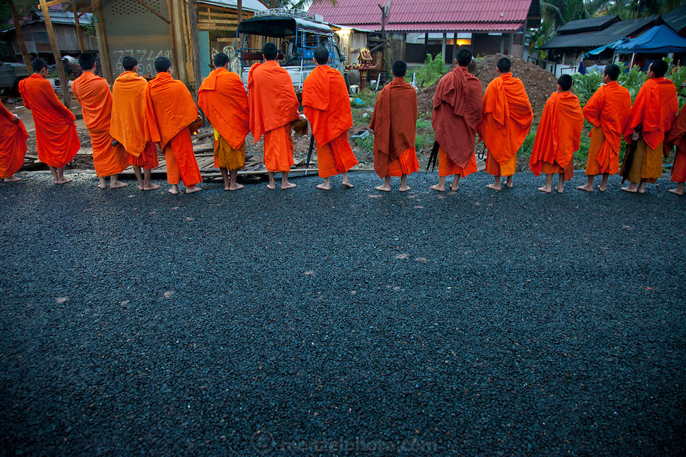 "In Ban Phan Luang, across the Nam Khan River from Luang Prabang, Laos. Every morning at dawn, Buddhist monks walk down the streets collecting food alms from devout, kneeling Buddhists. In neighborhoods, after receiving food, they line up and chant a blessing towards the benefactor's house. They then return to their temples (also known as ""wats"") and eat together. This procession is called Tak Bat, or Making Merit."