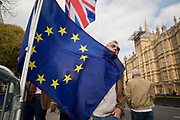 As MPs decide on how to progress with Brexit parliamentary procedure, and EU flag catches the face of a passer-by outside the UK Parliament in Westminster, on 28th March 2019, in London, England