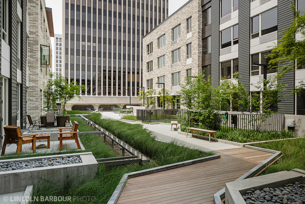 A walkway through an apartment building outdoor space.  Private patios line the path.  Very calm and serene urban space.