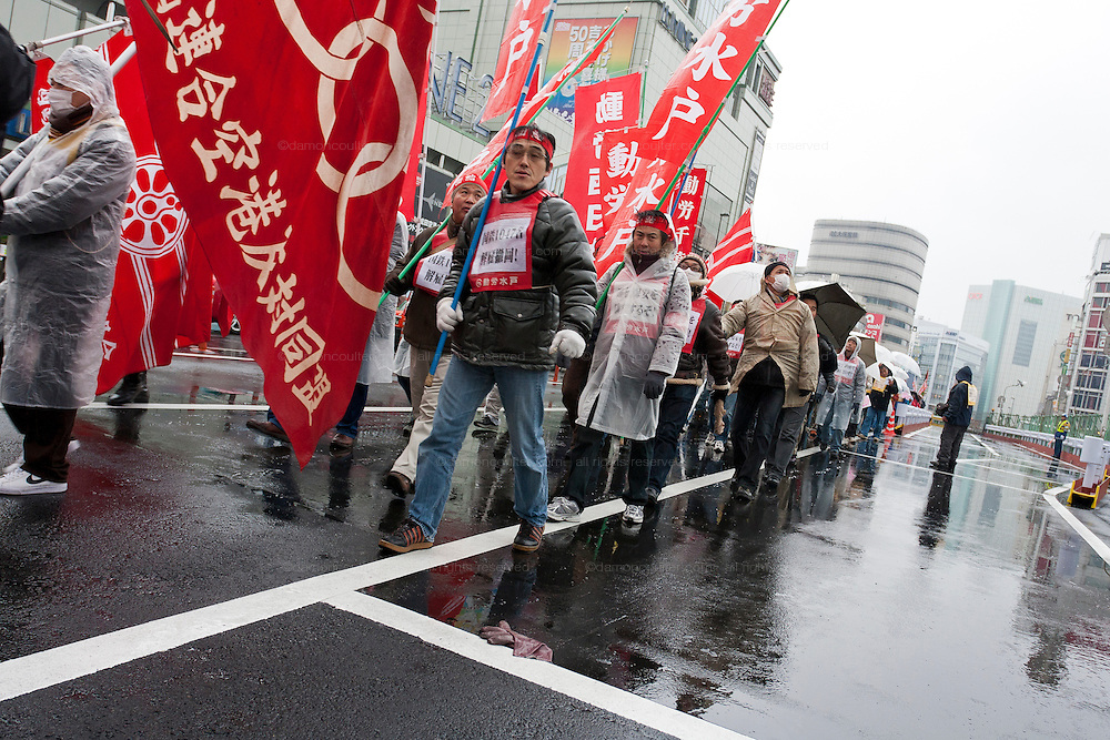 Union activists march at a demo rally organized by Doro Chiba labour union to protest the outsourcing of what they consider essential safety and repair work and fight against rationalization of JR (Japan Railways) business. They also protested for the reinstatement of 1,047 national railway workers who lost their jobs in 1987. Shinjuku, Tokyo, Japan Saturday, February 13th 2010