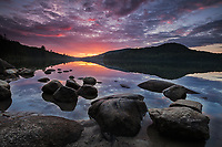 Purple clouds at sunset with mirror like reflection on Kettle Pond in Groton State Forest, Vermont
