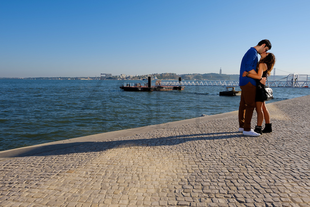 A couple  by the Tagus riverside. Terreiro do Paço, the largest Lisbon square, and is one of the most well-know place to visit in Lisbon.