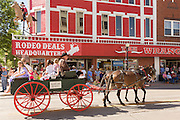 A wagon pasts the Wrangler western wear store during the Cheyenne Frontier Days parade through the state capital July 23, 2015 in Cheyenne, Wyoming. Frontier Days celebrates the cowboy traditions of the west with a rodeo, parade and fair.
