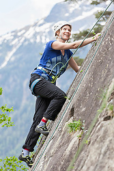 Female rock climber scaling a rock face at Oberried climbing garden, Otztal, Tyrol, Austria