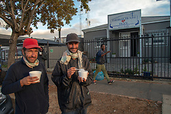 """(L to R) Jayson Tucker and Mark Schoeman, who both live on the streets, eat breakfast outside Thomas House of Hope, in Somerset West, Western Cape, on Tuesday morning, May 5, 2020. Thomas House normally provides programs through which people living on the streets can work in exchange for tokens that they can use for meals, ID books, clothing, toiletries and showers. But during lockdown, the centre has had to suspend its activities to simply serve meals to those who are hungry. """"I used to come here before lockdown,"""" says Tucker. """"We work for the garden (a community  food garden)."""" But now people show up for meals that don't work here, he adds. """"They are not doing something for it because of lockdown,"""" he says. PHOTO: EVA-LOTTA JANSSON"""