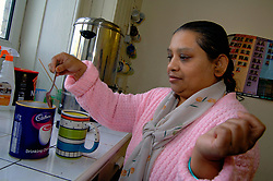 Woman with learning disabilities making hot chocolate in community centre; Bradford; Yorkshire UK
