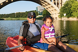 Father and daughter in kayak on Trinity River near downtown Fort Worth and the Trinity Trails, Fort Worth, Texas, USA.