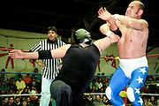 Two 2 male wrestlers in an arm lock referee in background. Lucha Libre wrestling origniated in Mexico, but is popular in other latin Amercian countries, including in La Paz / El Alto, Bolivia. Male and female fighters participate in the theatrical staged fights to an adoring crowd of locals and foreigners alike.