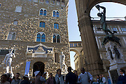 "Above tourists from south Asia, we see Michelangelo's David, Baccio Bandinelli's Hercules & Cacus and Benvenuto Cellini's Perseus with the Head of Medusa statues stand in Piazza della Signoria, beneath the fortress palace Palazzo Vecchio. Piazza della Signoria is an L-shaped square in front of the Palazzo Vecchio (""Old Palace"") which is the town hall of the city. This massive, Romanesque, crenulated fortress-palace is among the most impressive town halls of Tuscany. Overlooking the square with its copy of Michelangelo's David statue as well the gallery of statues in the adjacent Loggia dei Lanzi, it is one of the most significant public places in Italy, and it host cultural points and museums."