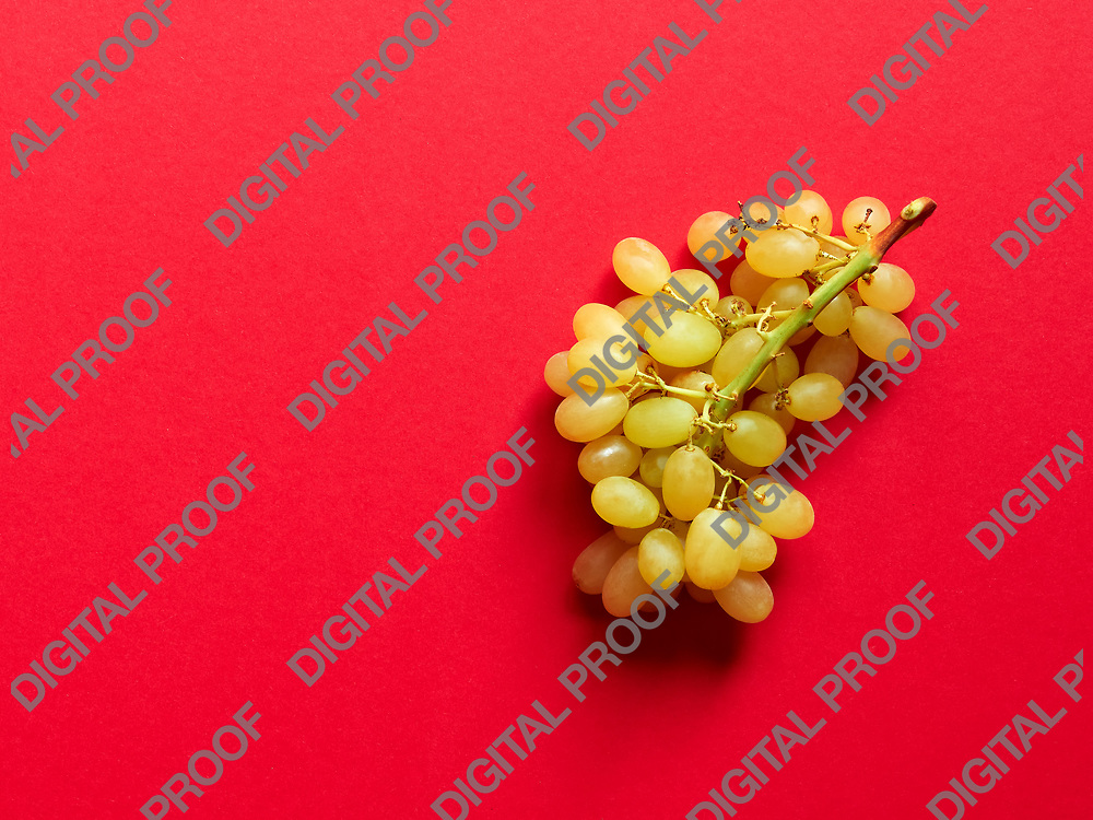 Above view of isolated set of a bunch of sweet seedless grapes in studio with red background