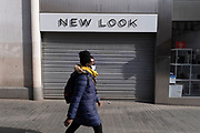 As the third national coronavirus lockdown in Birmingham continues, a few people still come to the city centre wearing face masks to visit the few essential shops that remain open as non essential shops such as fashion retailer New Look remain closed as the country awaits the easing of lockdown restrictions on 24th March 2021 in Birmingham, United Kingdom. Following the recent surge in cases including the new variant of Covid-19, this nationwide lockdown, which is an effective Tier Five, came into operation yesterday, with all citizens to follow the message to stay at home, protect the NHS and save lives.