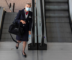 © Licensed to London News Pictures. 24/07/2020. London, UK. BA air crew wear masks in Terminal 5 at London Heathrow on their way to work as face masks become compulsory today in airports, shops, takeaway cafes and supermarkets and enforced by the Police, with anyone who fails to wear one liable to a £100 fine. Photo credit: Alex Lentati/LNP