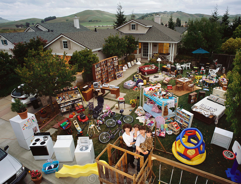 Usa.mw2.18.120.xs..The Caven Family with all of their material possessions, except for more boxes of books stored in the garage, American Canyon, California. Craig Caven, 38, and Regan Ronayne, 42, and their two children, Andrea, 5, and Ryan 3, live in a multi-cultural bedroom community called American Canyon, California, about one hour north of San Francisco. The photograph was made by Peter Menzel and patterned after his 1994 book, Material World: A Global Family Portrait. {{Until 1995, the Caven's were living in San Diego, California, where they met while in school at the University of California, San Diego. Since then, they have lived in American Canyon. Regan (pronounced with a long ?e?) Ronayne works a part-time schedule as a college counselor at UC Berkeley, California, and Craig is a drama and history high school teacher in a school district north of American Canyon. Their two children attend a daycare center on the days that Regan works. Both parents have a substantial commute from their single-family home in American Canyon, California. They share childcare, but Regan is the main caregiver; she worked half time after Ryan was born and only recently has returned to working 4 days a week. Craig's position as drama teacher keeps him at work late at night during play rehearsals and performances; it's not unusual for him to get home after 9 p.m. although his day starts before 8 a.m.}} .{{Do the Cavens have a most treasured possession? Craig would choose his large collection of books that threatens to overwhelm the house. Regan chooses the family photo album. A small army of McDonald's Happy Meal toys inhabits a corner of the kitchen. There's a wooden swing and climbing set. The family has three bedrooms, two bathrooms, a kitchen, a dining room/living room combination, a study and a garage. The Cavens are considering putting a second story on their house, which at 1100 square feet is bursting at the seams.}}.