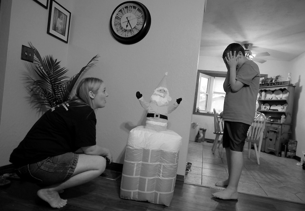Parker Roos, who suffers from Fragile X, laughs after setting up one of his inflatable lawn toys in the house as his mother Holly looks on at their home in Canton, Illinois, April 3, 2012.  REUTERS/Jim Young