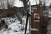 Roma squat in the snow in one of the largest Roma encampments 'bidounvilles' outside Paris. Winter, Sarcelles, Paris suburbs, France<br /><br />Eastern european Roma migrants, often from Romania and Bulgaria, searching for better opportunities, they move near to western european cities. They typically are poor and live in squats, here around the periphery of Paris, in the suburbs 'banlieu' where they typically build ramshackle homes from recycled wooden panels and corrugated iron, or sometimes benders made from branches covered in tarpaulins. They live in woods and forest, industrial estates or derelict buildings. Life is especially difficult for them in the harsh conditions of winter and rain. Most of these camps get destroyed by police and Roma are eventually evicted, some deported back home or moving on to build another home. They often survive by recycling metal and electronic goods, selling recycled clothes and objects they find in trash bins, or through begging or playing music on the city streets or inside metro stations. Paris, France
