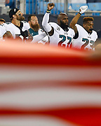 Malcolm Jenkins, Chris Long and Rodney McLeod react during the national anthem.