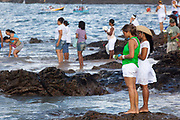 Young Brazilian women making offerings of flowers to the sea in honour of Yemanja. February 2nd is the feast of Yemanja, a Candomble Umbanda religious celebration, where thousands of adherants visit the Rio Vermehlo Red River to pay their respects to Yemanja, the Orixa goddess of the Sea and water.