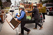 Amish men unload furniture during the Annual Mud Sale to support the Fire Department in Gordonville, PA.