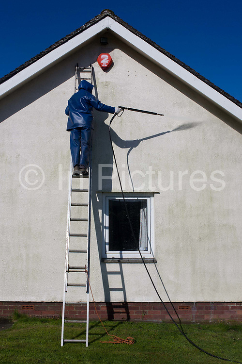 A middle-aged man power washes the white render on the exterior of his bungalow home. In strong sunshine, we see the gentleman up a ladder leaning against the white wall that needs the high-pressure contact from the hose. After washing down with a cleaning solution, he washes away the stained surface exposed to weather while wearing protective clothing.