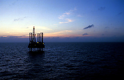 Stock photo of a silhouette of a jack up on the ocean