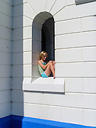 A young girl sits in a windo at the Byron Bay Lighthouse, Byron Bay, NSW, Australia