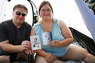 """Eric Ellis and wife Kim display pictures of their in-vitro fertilized (IVF) egg and their resulting son as they wait in a tent in line for an open casting session for season 11 of """"The Biggest Loser"""" television show in Broomfield, Colorado July 17, 2010. The couple said they wanted to lose weight on the show in the hope of having a second child, this time without expensive and difficult IVF. Over 600 people, many spending the night on the sidewalk outside the hall applied for a chance to be on the show and win $250,000.  REUTERS/Rick Wilking (UNITED STATES)"""