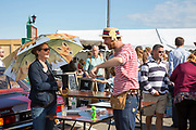 A woman uses an umbrella to shade from the sun at the 2017 Art Car Boot Fair, Folkestone, Kent.
