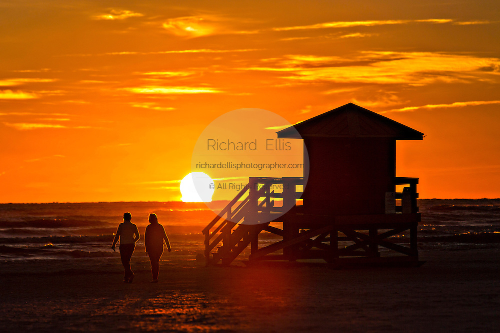 A couple is silhouetted by the sunset over Siesta Key beach in Sarasota, Florida