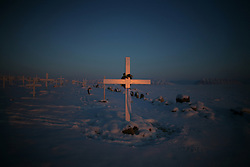 The long light from the twilight sun is reflected in the fresh paint of a new cross in the cemetery outside Qaanaaq, Greenland. A changing climate - which shows itself in warming temperatures, earlier summers, later winters, and shrinking and thinning sea ice - threatens the livelihoods and traditions of some of the last subsistence hunters on Earth, the Polar Inuit communities of far Northwest Greenland.