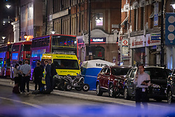 © Licensed to London News Pictures. 21/07/2021. London, UK. Police officers talk in front of an ambulance and forensic tent at the scene following a fatal stabbing on Brixton Road, Brixton. Metropolitan Police Service (MPS) were called at 20:18BST to reports of an assault close to Brixton Underground Station. Despite efforts from police officers, paramedics from London Ambulance Service (LAS) and London's Air Ambulance the man was pronounced dead at the scene at the 20:45BST. Photo credit: Peter Manning/LNP