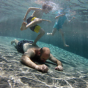 A father swimming underwater while playing with his son and daughter in his back yard family swimming pool. Connecticut, USA. Photo Tim Clayton