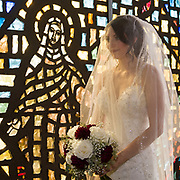 bride by stained glass window at St. Charles Borromeo Catholic Church, Boardman, Ohio by Tallmadge wedding photographer, Akron wedding photographer Mara Robinson Photography