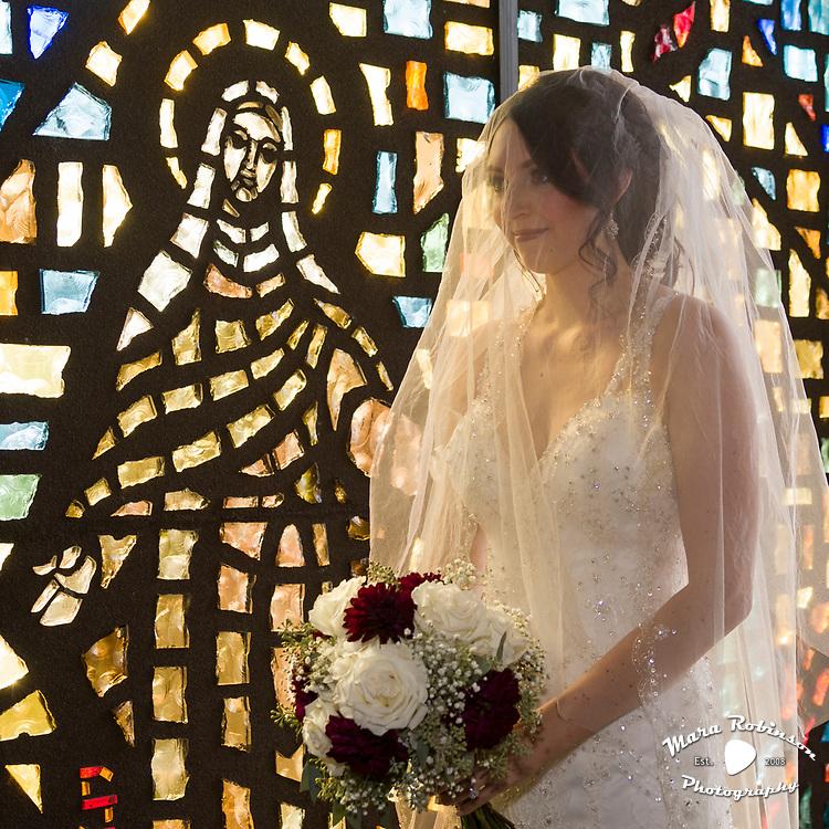bride by stained glass window at St. Charles Borromeo Catholic Church, Boardman, Ohio by Tallmadge wedding photographer, Akron wedding photographer Mara Robinson Photography