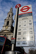 Beneath the church of St Mary le Strand, a bus stop at Aldwych, showing bus routes going south towards Waterloo and the Southbank in central London. With the numbers of bus services listed vertically on the sign post, we look from a low angle, up at the information post, a blue efternoon sky and the rising spire of St Mary's, its shiny clock showing 5.30pm. A red London bus can be seen lower left too, en route to its destination elsewhere in the capital. TfL-sponsored operators run more than 500 services and the word bus is derived from the word Onmibus (the Latin for 'everyone').
