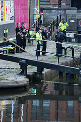 "© Licensed to London News Pictures . 06/10/2013 . Manchester , UK . Police wait as the lock is drained , to make the recovery . Police pull a body from The Bridgewater Canal in Manchester , adjacent to the City's "" Gay Village "" . The body was spotted yesterday (6th October) afternoon and a cordon was erected as specialist police divers made the recovery . Photo credit : Joel Goodman/LNP"