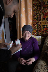 Siminova Nadiersha receives a visit from Doctor Khachatur Malakyan (c) and nurse Andrei Bogma (r) during an MSF home visit to check her blood sugar levels and deliver medecines to her. She lives alone in Dabelsevo, suffering from hyper tension and diabetes. She is only able to make it outside in her immediate neighbourhood and cannot walk far . Since the conflict in their city residents rely on humanitarian assistance in the form of food distributions and medical treatment due to shortages and lack of drugs and medical professionals in the town.