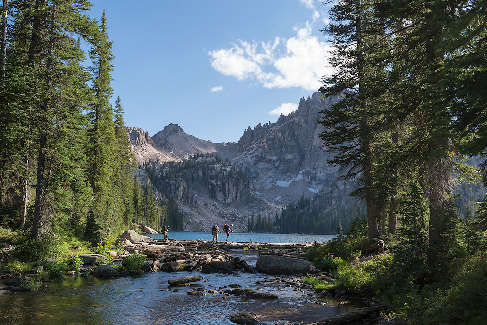 Backpackers crossing logs at the outlet of Baron Lake in Idaho's Sawtooth Mountains.
