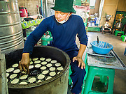 "28 OCTOBER 2014 - BANGKOK, THAILAND:  A worker puts cakes into the traditional oven at the Pajonglak Maneeprasit Bakery in Bangkok. The cakes are called ""Kanom Farang Kudeejeen"" or ""Chinese Monk Candy."" The tradition of baking the cakes, about the size of a cupcake or muffin, started in Siam (now Thailand) in the 17th century AD when Portuguese Catholic priests accompanied Portuguese soldiers who assisted the Siamese in their wars with Burma. Several hundred Siamese (Thai) Buddhists converted to Catholicism and started baking the cakes. When the Siamese Empire in Ayutthaya was sacked by the Burmese the Portuguese and Thai Catholics fled to Thonburi, in what is now Bangkok. The Portuguese established a Catholic church near the new Siamese capital. Now just three families bake the cakes, using a recipe that is 400 years old and contains eggs, wheat flour, sugar, water and raisins. The same family has been baking the cakes at the Pajonglak Maneeprasit Bakery, near Santa Cruz Church, for more than 245 years. There are still a large number of Thai Catholics living in the neighborhood around the church.  PHOTO BY JACK KURTZ"