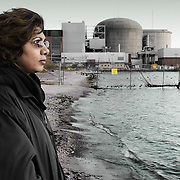 A woman standing on a beach shared by a nuclear power plant.