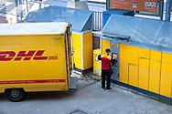 Germany, Cologne, a DHL parcel service driver supplies a Packstation in the district Deutz.<br /> <br /> Deutschland, Koeln, ein DHL Fahrer beliefert eine Packstation im Stadtteil Deutz.