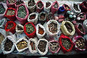"""A """"barefoot doctor's"""" (traditional healer's) display of herbs and roots in the Sunday market in Menghan village, Xishaungbanna, China. Image from the book project Man Eating Bugs: The Art and Science of Eating Insects."""