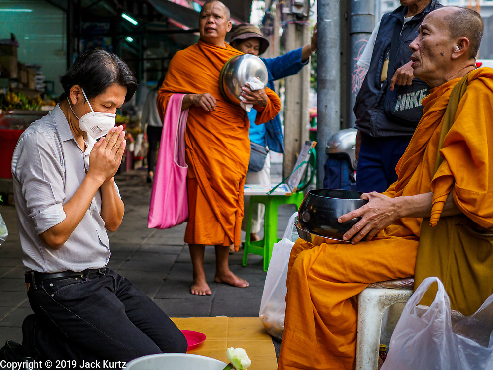 31 JANUARY 2019 - BANGKOK, THAILAND:   A man wearing a breathing mask because of Bangkok's air pollution prays after presenting food to a monk in Bangkok. The Thai government has closed more than 400 schools for the rest of the week because of high levels of pollution in Bangkok. At one point Wednesday, Bangkok had the third highest level of air pollution in the world, only Delhi, India and Lahore, Pakistan were worst. The Thai government has suspended some government construction projects and ordered other projects to take dust abatement measures. Bangkok authorities have also sprayed water into the air in especially polluted intersections to control dust. Bangkok's AQI (Air Quality Index) Thursday morning was 180, which is considered unhealthy for all people.   PHOTO BY JACK KURTZ