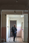 """Alexander Alexaninan, a 62 years old man is seen smoking in the corridors of the previously abandoned building of """"SOVIET Hotel"""" in Metsamor. He is father of three children from Aygestan, which is in the province of Askeran in Nagorno Karabakh region. He was 34 of his age when he lost his leg in 1992 when an Azerbaijani artillery shell hit him in the frontline. (Photo/ Vudi Xhymshiti)"""
