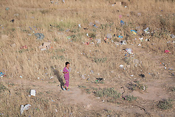 © Licensed to London News Pictures. 25/06/2014. Khanaqin, Iraq. A young Iraqi refugee walks through wasteland next to a refugee camp on the outskirts of Bahari Taza village in Iraq. Located on the outskirts of Khanaqin, a town just 20 minutes from the front-line of the battle with ISIS insurgents, the Bahari Taza refugee camp, and its satellite camps, now house around 600 families from southern Iraq. Built by the local village leader to meet the influx of refugees from nearby Jalawla and Saidia, where intense fighting is still taking place. Turkman, Arab and Kurd, both Sunni and Shia, all live together in tents, barns and unfinished buildings waiting for the conflict to end. Photo credit: Matt Cetti-Roberts/LNP