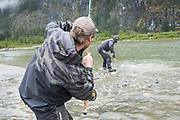 Pat Bogdan helps land a bright BC chinook salmon as David Page keeps the tension on.